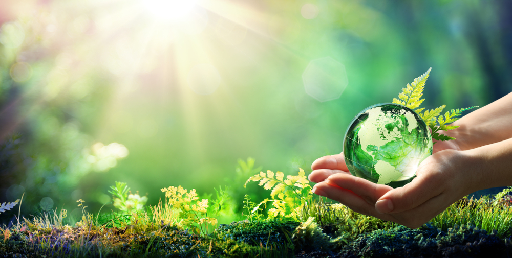 holding a glass ball in a clean countryside environment helped by recycling metal